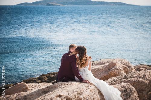 Plakat Całowanie para siedzi na skale z tyłu na piękny krajobraz seascape