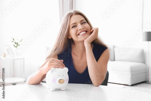 Fotografía  Young woman with piggy bank at table