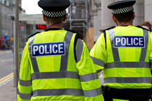 Police Officers In Hi-visibility Jacket Patrolling In The City. Police Officers In Duty. UK Police