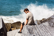Man Sitting On Stones At Sea
