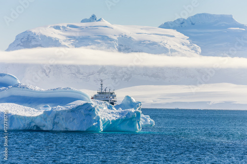 Poster Glaciers Blue antarctic cruise vessel among the icebergs with glacier in background, Neco bay, Antarctica