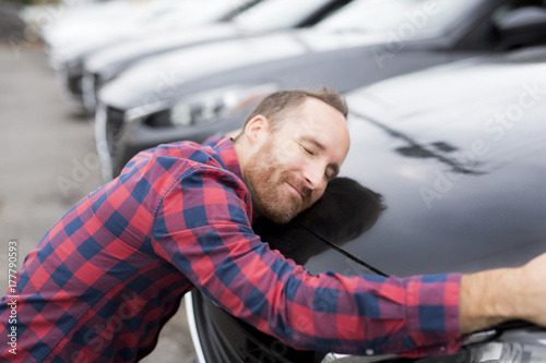 Fototapeta Happy young man hugging his car obraz