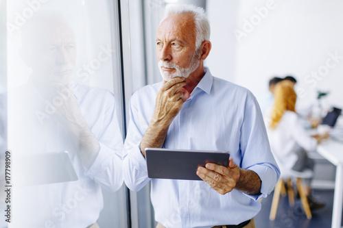 Plakat Starsza biznesmen pozycja okno z cyfrową pastylką w jego ręce