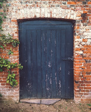 A Weathered Door In An Old Brick Wall.