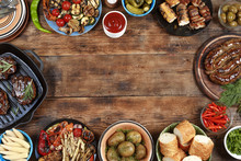 Outdoors Food Concept. Delicious Barbecued Steak, Sausages And Grilled Vegetables On A Wooden Picnic Table With Copy Space, Top View