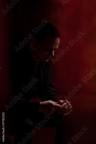 Fotografie, Obraz  Portrait of handsome catholic priest or pastor with dog collar, dark red background