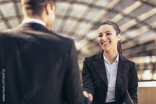 Foto  Two smiling young business people shaking hands while standing outdoors