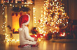canvas print picture child girl  sitting  back in front of  Christmas tree on Christmas Eve