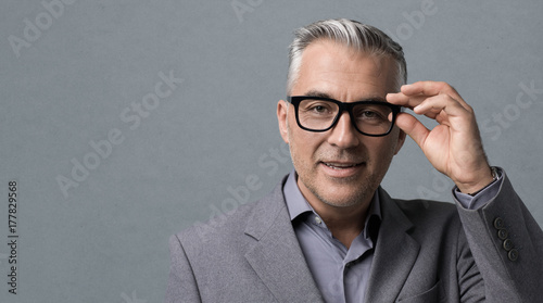 Cuadros en Lienzo Smart businessman with glasses posing