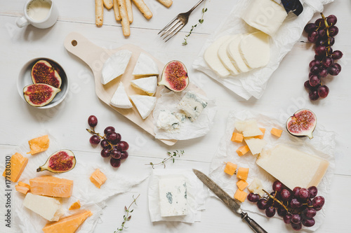 Various types of cheese with fruits and snacks on the wooden white table. Top view