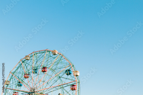 Ferris wheel detail against blue sky at an amusement park