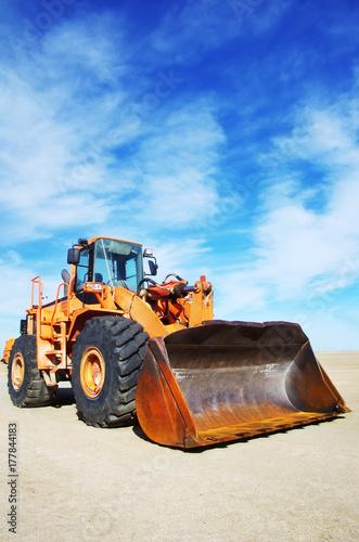 Fotografía  Orange loader bulldozer with cloud sky