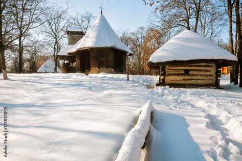 Fototapeta Mały drewniany kościół i chata pokryte śniegiem w Muzeum Wsi, skansen etnograficzny znajduje się w Bukareszcie, w Rumunii.
