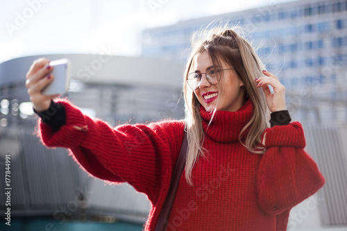 Canvas Prints Textures A beautiful girl makes selfie in the rays of the autumn sun. Red sweater and abstract architecure.
