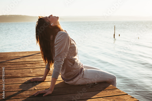 Girl on a jetty listening to music on her smartphone