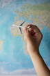 Hand holding a small airplane in front of the world map