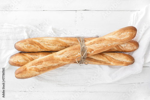 Fotografie, Obraz  Freshly baked French baguettes on white wooden table. Top view