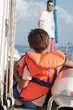 Boy sitting on a sailboat in a life jacket with father in the background