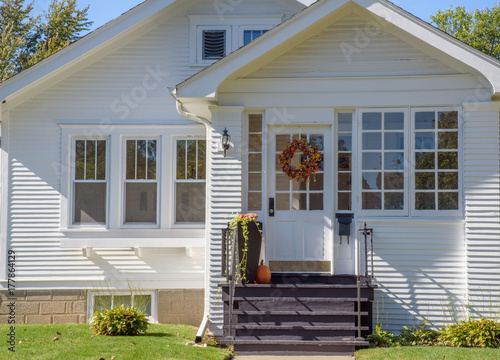 Fototapeta Exterior street view of cute bungalow home decorated for fall with Autumn wreath