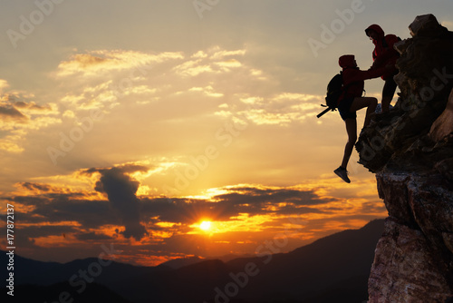 Foto Teamwork hiking help each other trust assistance at mountains and beautiful sunrise,teamwork and hiking concept