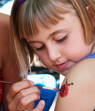 Little Girl Getting A Lady Bug Painted On Her Arm At The Harvest Festival