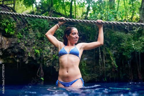 Obraz na plátně Girl playing with rope in Cenote sinkhole