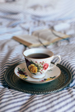 Black Tea In China Cup On Vintage Tray With Open Book And Glasses