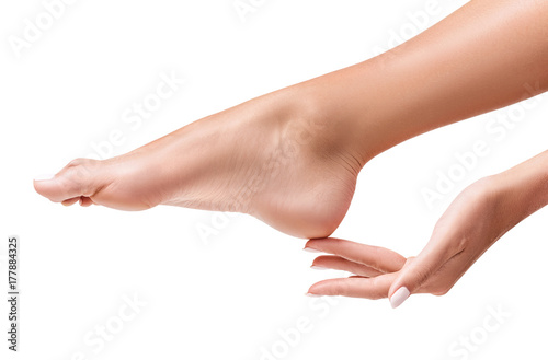 Fotografia Perfect female feet. Hand touches elegant leg.