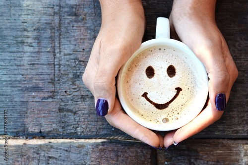 Obraz na plátně  Woman hands holding one cappuccino cup with optimistic face on wooden table