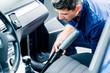 Mann beim Aussaugen von Auto bei der Reinigung und Pflege