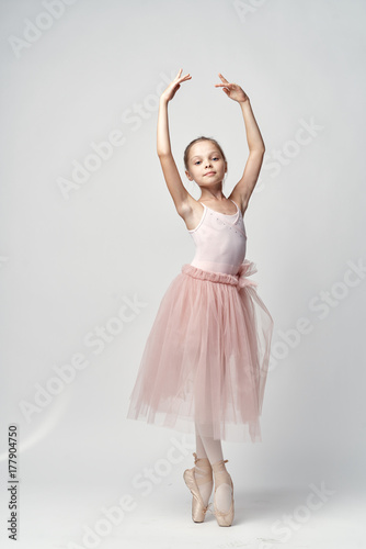 Photo little ballerina in a light bundle and pointe poses with her arms raised