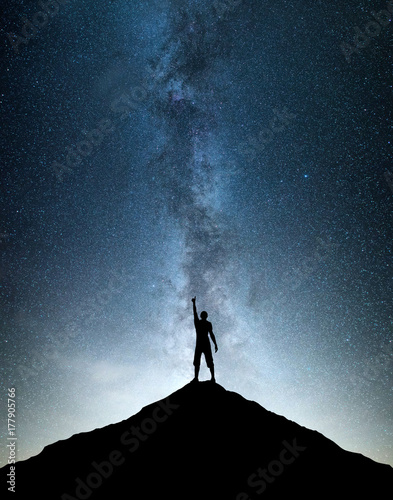 Silhouettes of winner on mountain peak. Sport and active life concept on the night sky background.