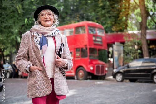 Fotografie, Tablou  Excited senior lady standing on street