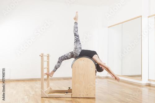 Photo  Beautiful woman performing pilates exercise, training on barrel equipment