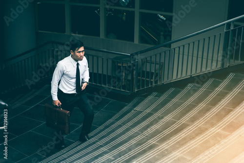 Young Asian Businessman Holding Brown Leather Bag Walking On