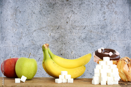 Fototapeta Choose healthy fruits instead of unhealthy sweets with huge quantity of sugar