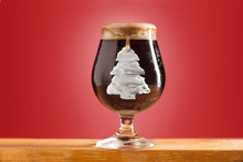 Glass Of Cold Frothy Dark Beer On An Old Wooden Table