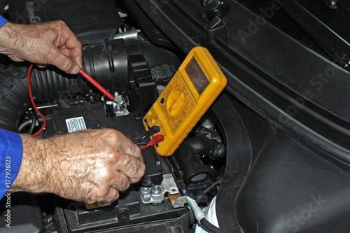 Mecnico Comprobando El Voltaje De La Batera Del Coche