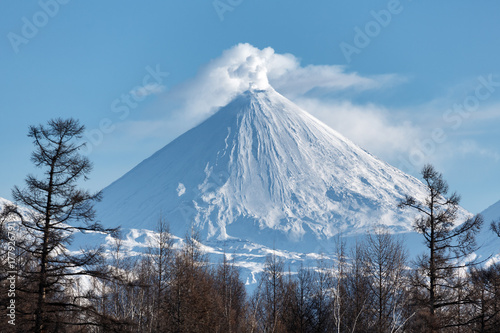 Spoed Foto op Canvas Vulkaan Winter volcanic landscape of Kamchatka Peninsula: view of eruption active Klyuchevskoy Volcano in sunny day clear weather. Eurasia, Russian Far East, Kamchatka Region, Klyuchevskaya Group of Volcanoes