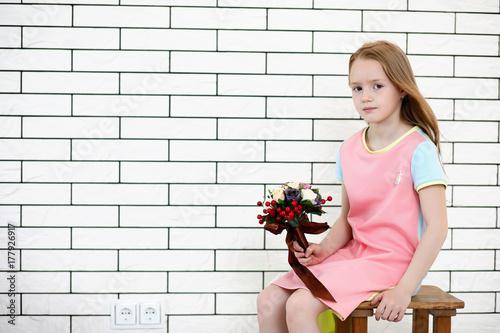 Fototapeta little girl is sitting on a chair obraz
