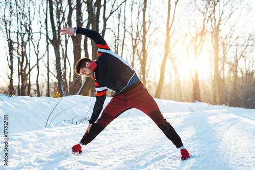 Zdjęcie XXL Elastyczny młody biegacz w odzieży sportowej ze słuchawkami rozciąganie z podniesionym ramieniem na śniegu pokryte zimą drogi rano.