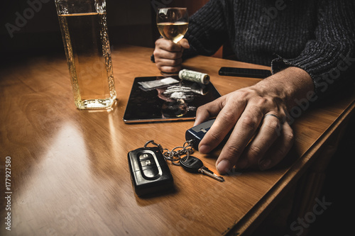 Poster de jardin Bar Man takes car keys after using cocaine drug and drinking whiskey. Drugs, alcohol and driving concept