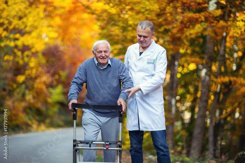 Fényképezés  Male nurse assisting senior patient with walker outdoor