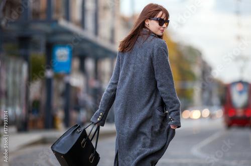 Obraz Trendy fashion woman in coat walking on the street, city scene - fototapety do salonu
