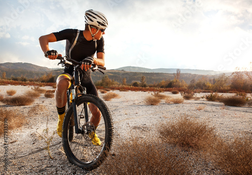 Printed kitchen splashbacks Cycling Young cyclist resting after riding a mountain bike over the desert.Sunset.