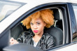 Close-up portrait of a beautiful african woman with curly hair in leather jacket driving a car