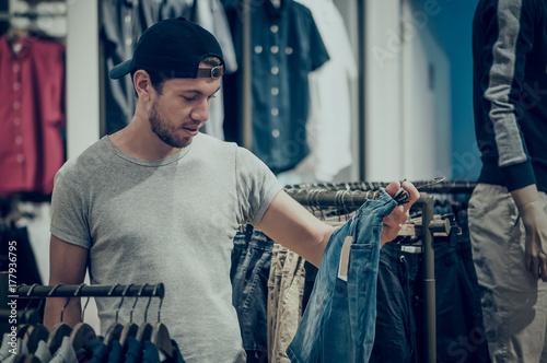 Plakat Młodego człowieka wybierać odziewa w zakupy centrum handlowym