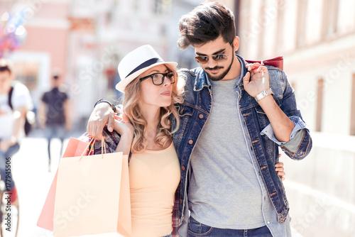 Fototapeta Portret szczęśliwa para z torba na zakupy w miasto ulicie.