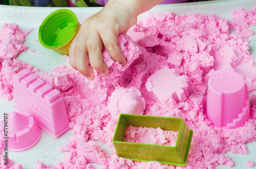 Child's hand playing with kinetic sand on the white table