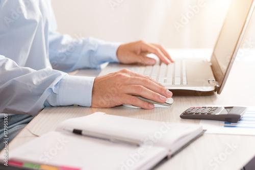 Plakat Biznesmen używa jego laptop
